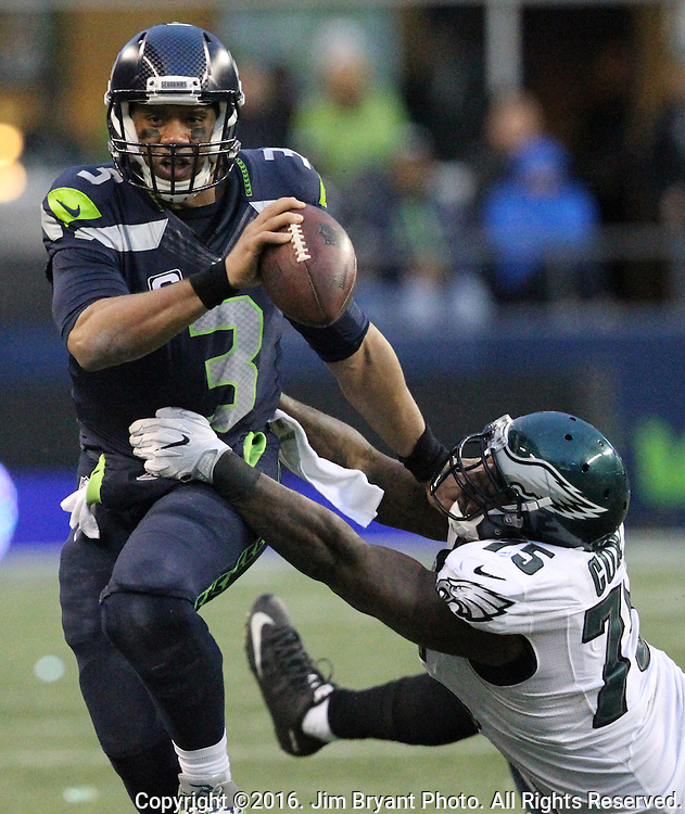 Seattle Seahawks quarterback Russell Wilson (3) stiff arms Philadelphia Eagles defensive end Vinny Curry (75)<br /> at CenturyLink Field in Seattle, Washington on November 20, 2016.  Seahawks beat the Eagles 26-15.  &copy;2016. Jim Bryant Photo. All Rights Reserved.