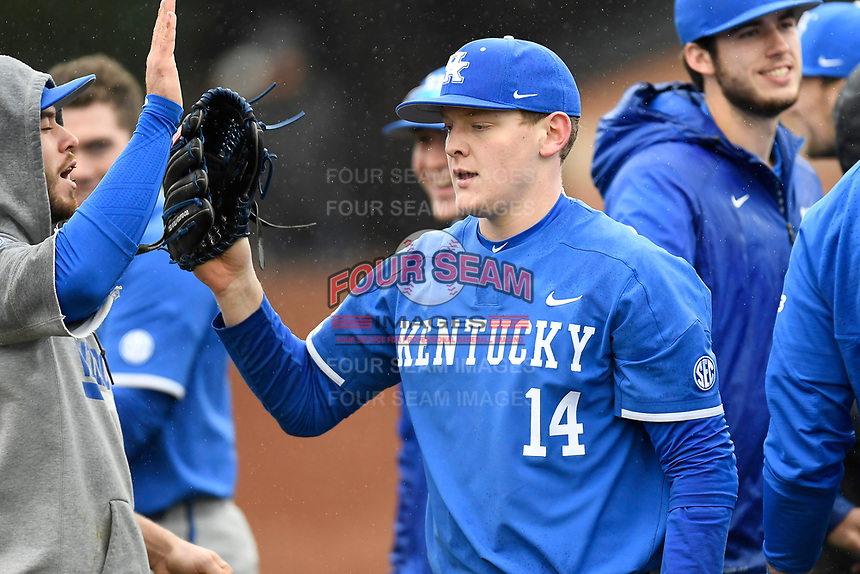 Starting pitcher Zack Thompson (14) of the Kentucky Wildcats is congratulated by teammates after a scoreless inning in a game in the rain against the University of South Carolina Upstate Spartans on Saturday, February 17, 2018, at Cleveland S. Harley Park in Spartanburg, South Carolina. Kentucky won, 6-5, in 10 innings. (Tom Priddy/Four Seam Images)