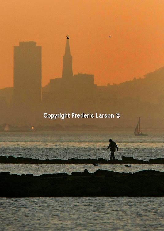 A man walks along the Albany Flats in Albany California.