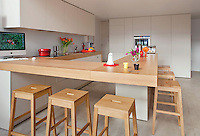 The thick oak breakfast bar which defines this open plan kitchen together with the seamless walls of storage is the work of Jean-Sébastien Gaubert
