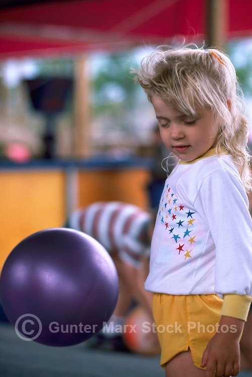 Young Blonde Girl, with Closed Eyes and Windblown Hair, standing in front of Purple Ball suspended in Mid Air by Air Blowing Machine (No Model Release Available)