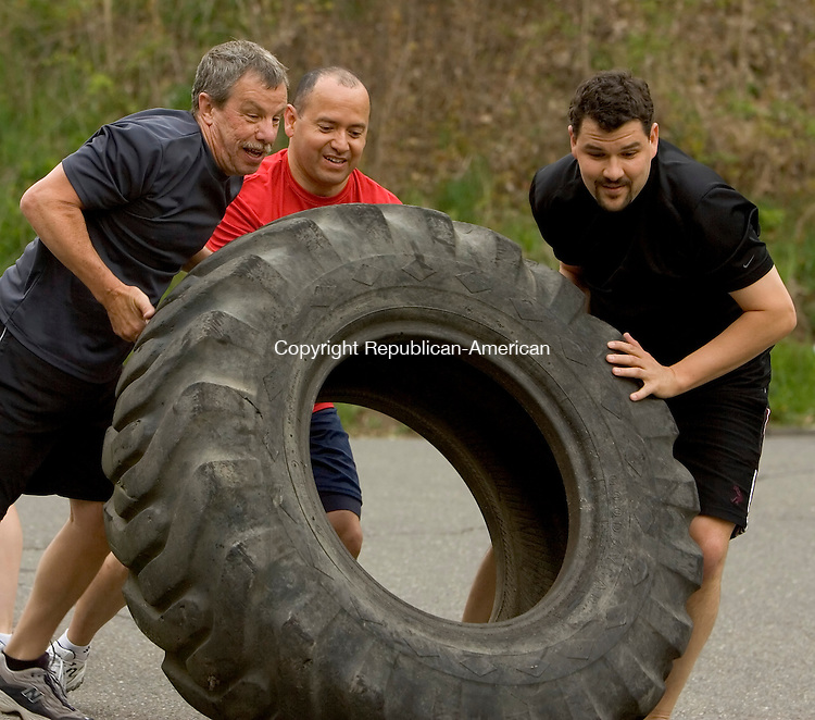 WATERTOWN, CT- 01 MAY 2008 --050108JS28-Rich Boucher, Ben Rodarte and Nathan Chmura, work as a team in the tire flip excersise during their workout at CrossFit in Watertown on Thursday. <br /> Jim Shannon / Republican-American
