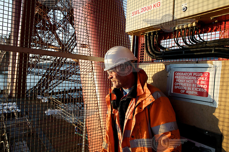 Hoist operator Neil 'Neily' Louden takes in the sunrise as the hoist transports workers between levels, on the 125 year old Forth Rail Bridge which spans the river Forth near Edinburgh. Network Rail, the operator of the rail track that leads over the bridge, has spent 10 years and GBP 130 million repainting the 230,000 square metres of steel and 6.5 million rivets on the bridge. The iconic red paint used on the bridge is made to match the red-oxide paint used over 100 years ago. The bridge will now need no further painting for at least 20 years.