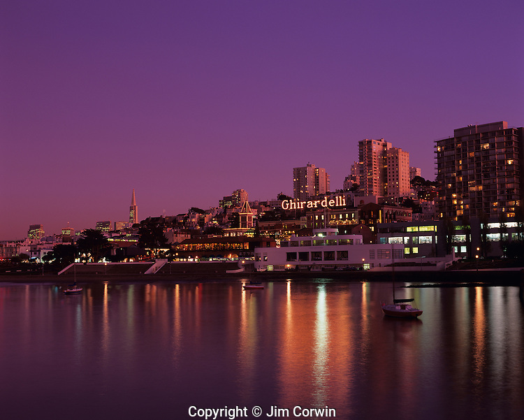 Ghiradelli Square at sunset with city lights reflected in bay, San Francisco, California USA