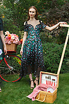 "Model poses in a hunter green and lilac rose garden fil coupé dress with grograin detail, from the Lela Rose Resort 2018 ""Garden Party"" collection in Jefferson Market Garden on June 7 2017, during Resort Fashion Week in New York City."