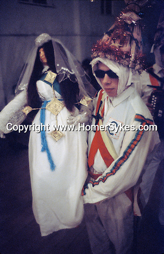 Biddy Boys 1970s. Killorglin Co Kerry Ireland. February 2nd festival to celebrate the Celtic Saint Bridgid. A doll - St Bridgid - is taken from house to house paraded through the street by Biddy Boys, receiving the effigy in to your home in considered lucky.