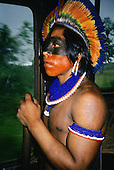 Altamira, Para State, Brazil. Kayapo warrior with face paint and feather headdress on a bus.
