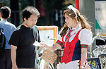"""August 30, 2011 - Tokyo, Japan - A maid cos-player hands out a leaflet to a man on the street. Akihabara is a well-known district in Tokyo for people who have obsessive interests particularly in manga, anime or video games. The Japanese term used for these types of people is called """"otaku."""" (Photo by Yumeto Yamazaki/AFLO)"""