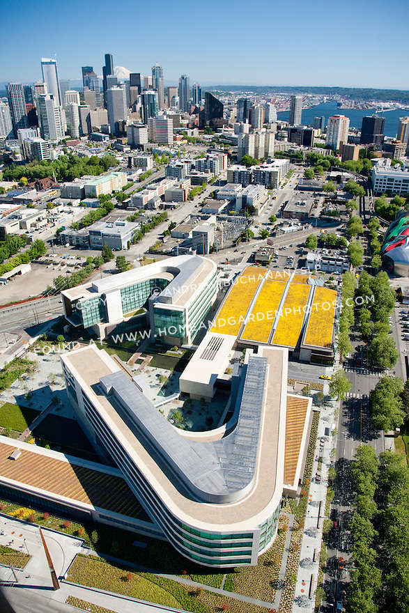 An aerial view of the Bill & Melinda Gates Foundation campus with the Seattle skyline, Mt. Rainier, and Puget Sound in the background.