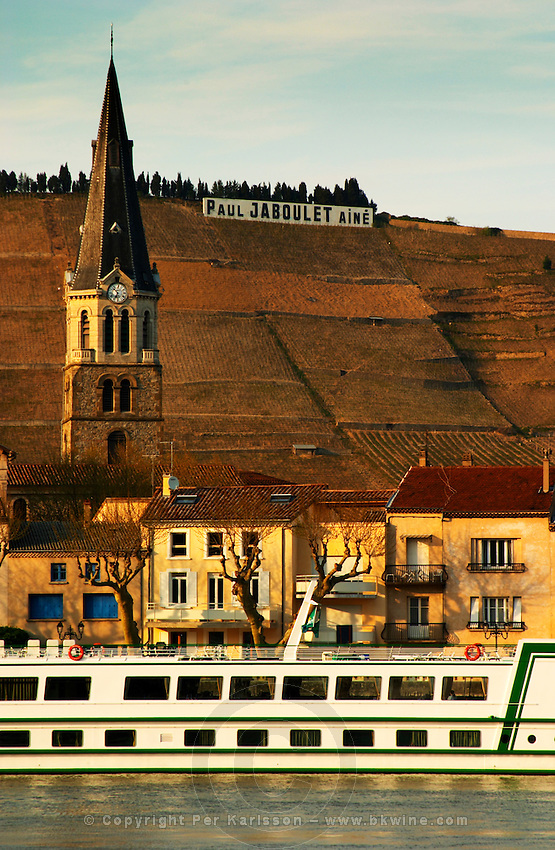 A view across the river from Tournon with a river cruise boat moored in Tain. The church in Tain and a sign with Paul Jaboulet Aine. The Hermitage vineyards on the hill behind the city Tain-l'Hermitage, on the steep sloping hill, stone terraced. Sometimes spelled Ermitage. Tain l'Hermitage, Drome, Drôme, France, Europe