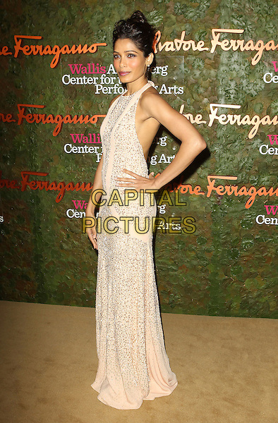 Freida Pinto<br /> Wallis Annenberg Center For The Performing Arts Inaugural Gala held at Wallis Annenberg Center For The Performing Arts,  Beverly Hills, California, USA, 17th October 2013.<br /> full length beige cream long maxi dress sleeveless beaded hand on hip nude<br /> CAP/ADM/KB<br /> &copy;Kevan Brooks/AdMedia/Capital Pictures