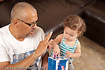 13 month old baby girl at home with father who is her primary caregiver talking about and playing with nesting stacking boxes holding up three fingers as he counts and she points at number 3 on box horizontal