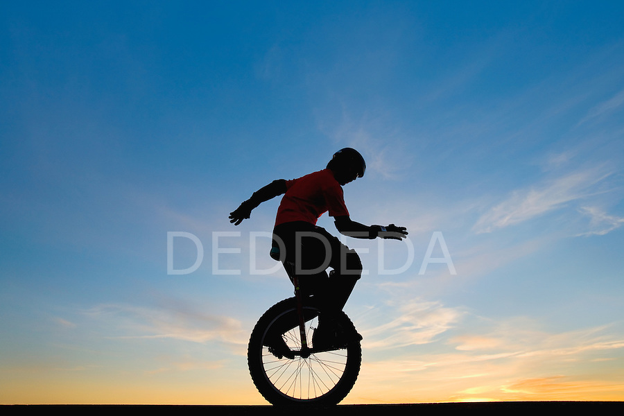 A young man rides his mountain unicycle at sunset.