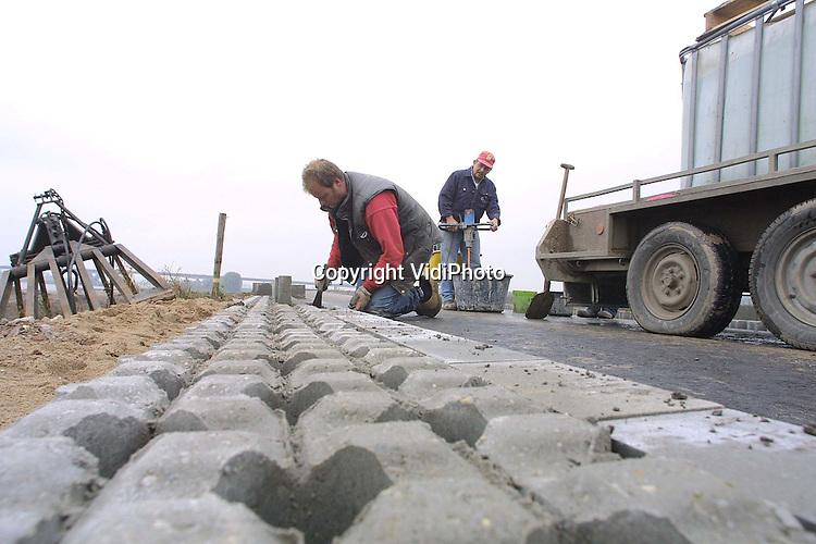 """Foto: VidiPhoto..ARNHEM - Stratenmakers werken in opdracht van Rijkswaterstaat met man en macht op de nieuwe Rijndijk bij Arnhem aan een 4 kilometer lang fietspad. Het fietspad loopt dwars door de natuur. In het kader van """"Ruimte voor de Rivieren"""", is de Rijndijk bij Arnhem zo'n 200 meter opgeschoven en krijgt de Rijn ter plaatse 50 procent meer ruimte. Als het rivierpeil van de Rijn stijgt, komt het fietspad voor een groot deel onder water te liggen. Het totale project kost zo'n 20 miljoen gulden en moet 15 november klaar zijn."""