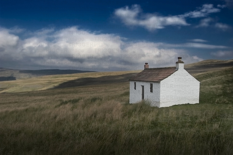 A small white crofters cottage in an open grassy landscape
