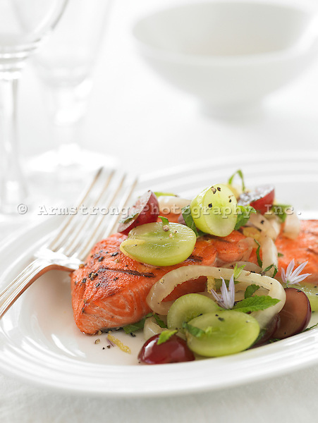Salmon, sauteed onion, grapes. With fork and wine glasses.
