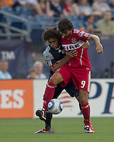 Chicago Fire midfielder Baggio Husidic (9) attempts to control the ball as New England Revolution defender Kevin Alston (30) pressures. In a Major League Soccer (MLS) match, the New England Revolution tied the Chicago Fire, 1-1, at Gillette Stadium on June 18, 2011.