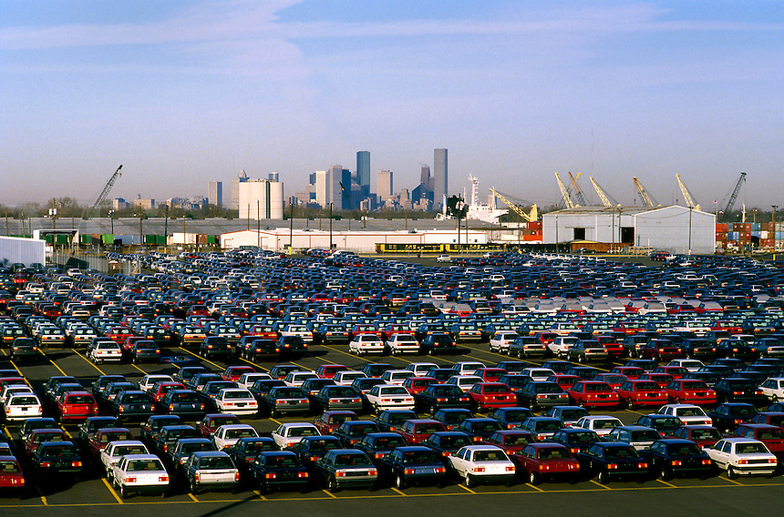 Aerial view of a new car storage lot at port, with downtown Houston in the background. Houston, Texas.