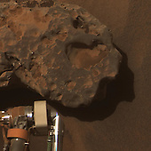 """This is an image of the meteorite that NASA's Mars Exploration Rover Opportunity found and examined in September 2010.  Opportunity's cameras first revealed the meteorite in images taken on Sol 2363 (September 16, 2010), the 2,363rd Martian day of the rover's mission on Mars. This view was taken with the panoramic camera on Sol 2371 (September 24, 2010).  The science team used two tools on Opportunity's arm -- the microscopic imager and the alpha particle X-ray spectrometer -- to inspect the rock's texture and composition. Information from the spectrometer confirmed that the rock is a nickel-iron meteorite. The team informally named the rock """"Oileán Ruaidh"""" (pronounced ay-lan ruah), which is the Gaelic name for an island off the coast of northwestern Ireland.  Opportunity departed Oileán Ruaidh and resumed its journey toward the mission's long-term destination, Endeavour Crater, on Sol 2374 (September 28, 2010) with a drive of about 100 meters (328 feet). This view, presented in approximately true color, combines component images taken through three Pancam filters admitting wavelengths of 601 nanometers, 535 nanometers and 482 nanometers. .Credit: NASA/JPL-Caltech/Cornell University via CNP"""