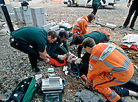 Emergency service personnel attend an incident where a construction worker fell from working on scaffolding and as a serious head injury, a cervical collar placed on him and whilst one paramedic performs CPR another is bagging him..This image may only be used to portray the subject in a positive manner..©shoutpictures.com..john@shoutpictures.com