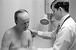 Male doctor examining shoulder and arm of shirtless elderly male patient in examination room