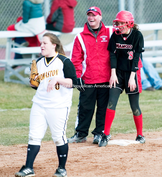 LITCHFIELD, CT- 10 APRIL 07- 041007JT12- <br /> Wamogo head coach Scott Marcucio congratulates Jordan Albano after she made it to third base after a bunt from her teammate Heather Crowell at Tuesday's game against Thomaston at Wamogo. In the foreground is Thomaston's third baseman Jamie Quirke.<br /> Josalee Thrift Republican-American