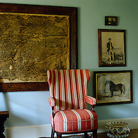 A red and white striped wing-backed armchair stands against a collection of framed antique prints