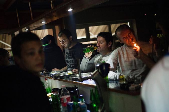Eine Gruppe junger Leute feiert am Samstagabend an der Bar im Cafe Que Pasa in Neum, Bosnien. Das Cafe Que Pasa ist der einzige Club in Neum. Der kleine Ort Neum liegt in Bosnien-Herzegovina und bildet den einzigen Zugang zum Meer des Balkanlandes. Auf einer Länge von 9 km durchschneidet der Ort das kroatische Staatsgebiet (Neum-Korridor) Seit dem EU-Beitritt Kroatiens ist Neum auf beiden Seiten von EU-Außengrenzen eingeschlossen. / A group of young people at the bar at Cafe Que Pasa in Neum, Bosnia. Cafe Que Pasa is the only club in Neum. The small city of Neum in Bosnia and Herzegovina is the only place in Bosnia, where the country has access to the adriatic sea. Over a length of 9 kilometers the area cuts Croatian territory in two pieces. Since Croatia became part of the European Union, the city of Neum is enclosed between two EU-boarders.