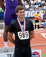 Neosho junior Justin Mckee smiles for the official photo after receiving his 8th place medal for the Class 4 Boys Long Jump. Mckee's best mark was 20-11.75.