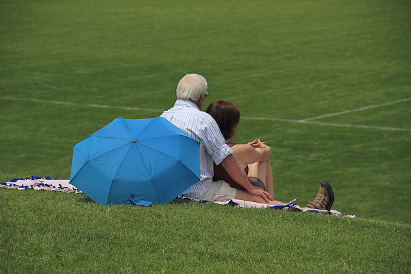 Senior couple sitting on blanket at sporting event, Denver, Colorado, USA. .  John offers private photo tours in Denver, Boulder and throughout Colorado. Year-round Colorado photo tours. .  John offers private photo tours in Denver, Boulder and throughout Colorado. Year-round.