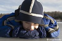 Happy young boy lying on the frozen lake ice