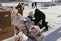 February 16, 2013  Volunteers Andi Malard (L) and Jennifer Ambrose stack musher food bags bound for Rainy Pass while other volunteers move supplies to waiting planes at the Willow airport as musher food, straw, HEET and people food is flown to the 4 checkpoints on the east side the Alaska Range. ..Photo Copyright Jeff Schultz  -- Do not reproduce without written permission