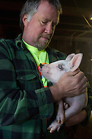 Farmer Ken Young with a piglet in Edgewood, Washington on April 4, 2015.