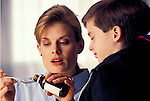 concerned mother pouring teaspoon of liquid medicine for young sick boy