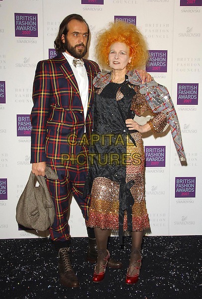 ANDREAS KRONTHALER & DAME VIVIENNE WESTWOOD.Arriving at the British Fashion Awards 2007 at the Horticulutral Hall London, Engalnd, .27th November  2007..full length red shoes black brown beaded dress hands on hips tartan.CAP/CAS.©Bob Cass/Capital Pictures.
