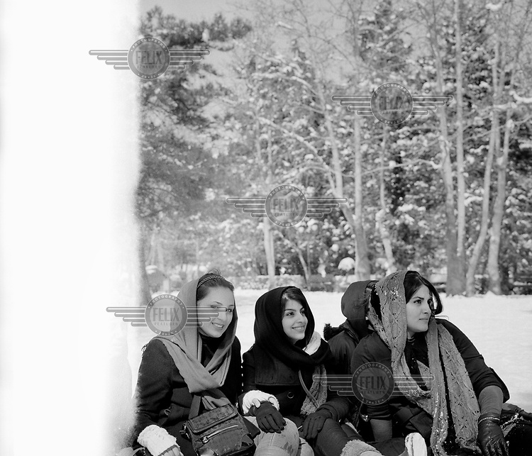 A group of young women, their hair daringly exposed, in a snow covered city park.