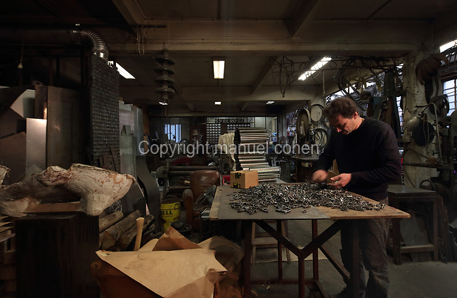 Nicolas Desbons, metalworker and artist, selecting steel pieces for a sculpture made from cross-sections of steel tubes manipulated into organic profiles and soldered together, in his Soleil Rouge workshop, photographed in 2017, in Montreuil, a suburb of Paris, France. Desbons works mainly in steel but often in conjunction with other materials such as fibreglass, glass and clay, using both cold metal and forge techniques. He produces both figurative and abstract sculptures as well as furniture and lighting. Picture by Manuel Cohen