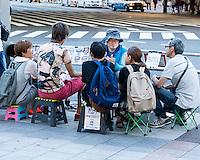 A street caricaturist surrounded by his clients. 500 yen per portrait.