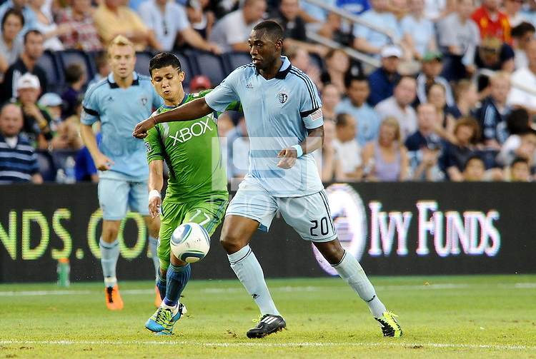 Birahim Diop (20) midfielder Sporting KC holds off Fredy Montero (17) ) forward Seattle Sounders... Sporting Kansas City were defeated 1-2 by Seattle Sounders at LIVESTRONG Sporting Park, Kansas City, Kansas.