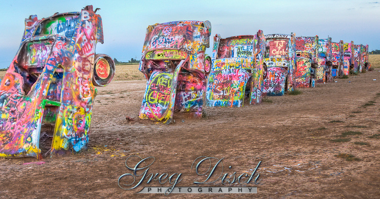 Cadillac Ranch is a public art installation and sculpture in Amarillo, Texas, U.S. It was created in 1974 by Chip Lord, Hudson Marquez and Doug Michels, who were a part of the art group Ant Farm, and it consists of what were (when originally installed during 1974) either older running used or junk Cadillac automobiles, representing a number of evolutions of the car line (most notably the birth and death of the defining feature of early Cadillacs; the tail fin) from 1949 to 1963, half-buried nose-first in the ground, at an angle corresponding to that of the Great Pyramid of Giza in Egypt.