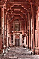 Fatehpur Sikri, Uttar Pradesh, India.  Corridor of the Jama Masjid (Dargah Mosque).  Hindu-style arches overhead, Islamic arch over the door.
