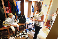 Heather Jacobs looks over a list of tasks as a reminder before she leaves for an evening of errands and activities with her five children.  Son Justin, 10, waits at left, while Keenan, 7, looks for his shirt.   Heather lost her husband, Eric, in a plane crash in 2006 when she was eight months pregnant with their youngest, Ella, and has since been raising her five young children on her own.