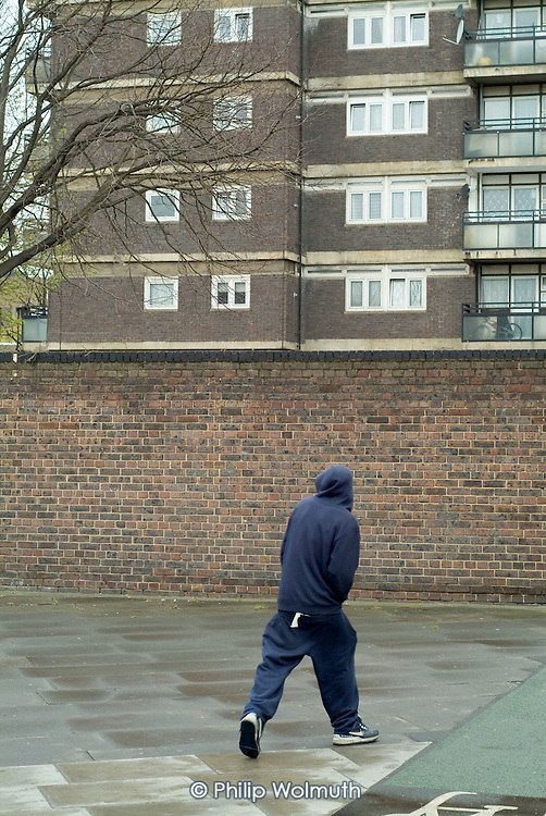 A young man in a hooded top walks into a housing estate in Whitechapel, in the London Borough of Tower Hamlets.