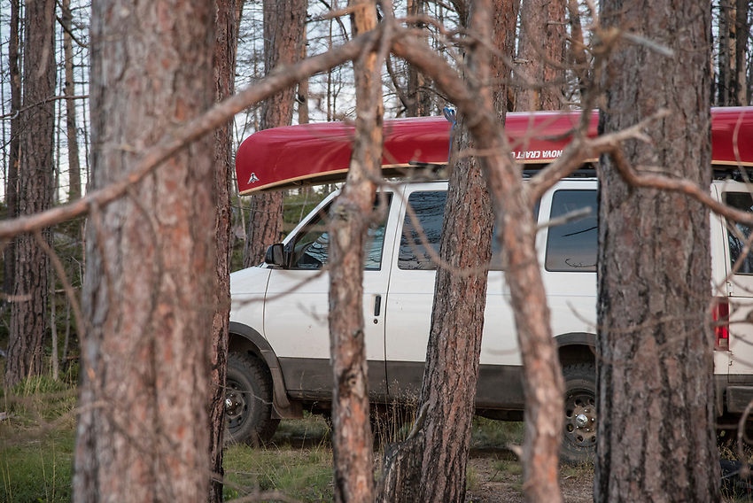 A 4x4 van with a red canoe at a backcountry campsite along Lake Superior on Michigan's Upper Peninsula.