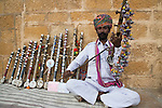 Rajasthani musician playing and selling chikara string instrument on street, Rajasthan, India --- Model Released
