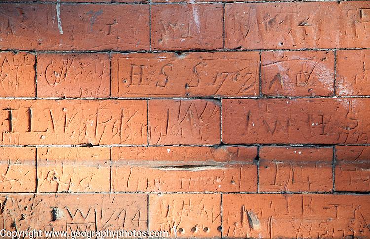 Eighteenth century children's graffiti scratched into red brick of former school building, Dedham, Essex, England