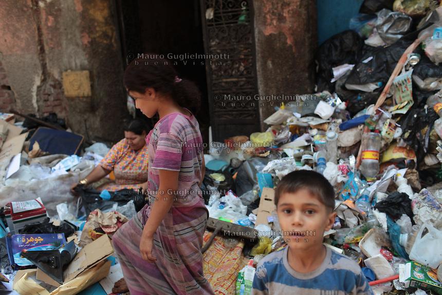2011 Mokattam Garbage City (alla periferia del Cairo) il quartiere copto dove si vive in mezzo alla spazzatura raccolta: due bambini in strada tra la spazzatura. Dietro di loro una montagna di rifiuti e una donna che divide l'immondizia.