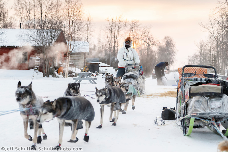Steve Watkins runs down the road and past teams parked on the banks of the Yukon river at the Tanana checkpoint as the sun rises behind him at 20 below zero on Wednesday morning March 11th during the 2015 Iditarod.<br /> <br /> (C) Jeff Schultz/SchultzPhoto.com - ALL RIGHTS RESERVED<br />  DUPLICATION  PROHIBITED  WITHOUT  PERMISSION