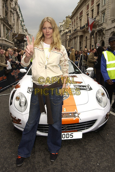 JODIE KIDD.At the Photocall for the Launch of Gumball Rally 3000, Pall Mall, London, England, April 30th 2006..full length cream beige jacket peace sign fingers gesture hand in pocket jeans trainers black and orange car.Ref: CAN.www.capitalpictures.com.sales@capitalpictures.com.©Can Nguyen/Capital Pictures