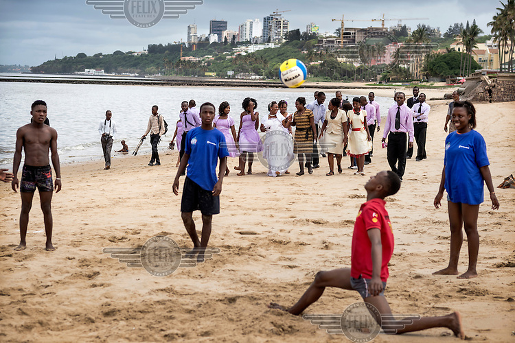 Young men play volleyball on a beach in Maputo with new residential buildings under construction in the background. Mozambique's economy is one of the fastest growing due to foreign investment and the discovery of natural reserves.